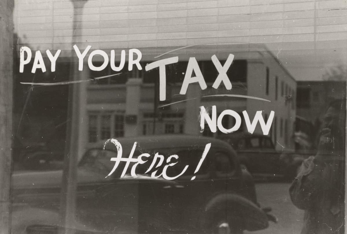 """Pay Your Tax Now"" text written on an old window"